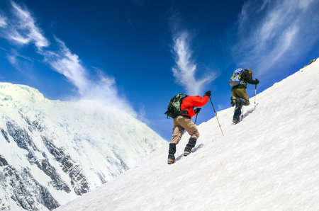 Photo pour Two mountain trekkers on steep snowed hill with dramatic sky background, Himalayas, Nepal - image libre de droit