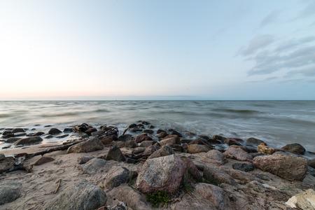 Photo pour Rocky beach with clouds and water - image libre de droit