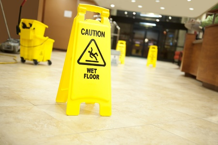 Lobby floor with mop bucket and caution wet floor signs, selective focus on nearest sign