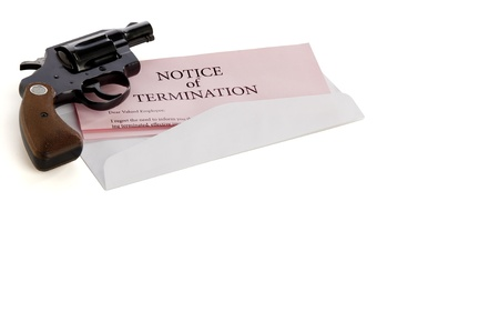 Pink slip termination notice lies on white background with a gun lying on top of it