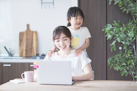 Photo pour Asian woman doing telework in home room while playing with her daughter - image libre de droit