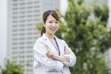 Photo pour Asian female healthcare worker in white coat posing outdoors - image libre de droit