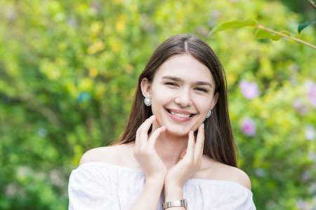 Photo pour A young woman wearing a white off-shoulder shirt and surrounded by plants - image libre de droit