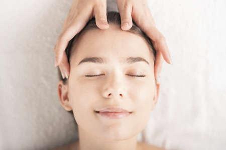 Photo pour Young woman having her head massaged at the beauty salon - image libre de droit