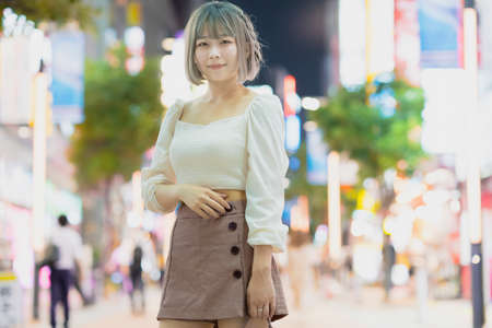 Photo for Young woman posing in the glowing cityscape of Tokyo at night - Royalty Free Image