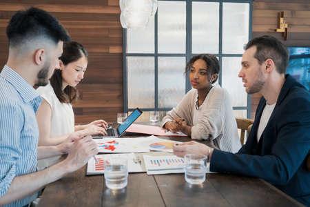 Photo pour Businessmen of various races meeting in a casual office space - image libre de droit