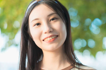Photo for Outdoor portrait of a young Asian woman with long black hair - Royalty Free Image