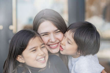 Photo pour Mom and 2 kids frolicking with a smile outdoors - image libre de droit
