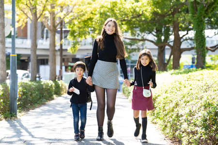 Photo pour Mother and two children walking outdoors holding hands with smile - image libre de droit