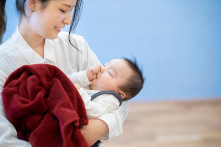 Photo pour Asian young mom hugging a sleeping baby in the room - image libre de droit