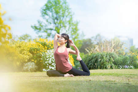 Foto de Young woman doing yoga in a green park on fine day - Imagen libre de derechos