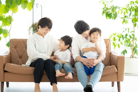 Photo pour Asian family frolicking on the couch - image libre de droit