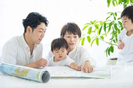 Photo pour Parents and children studying happy using maps / Parents and children planning trips using maps - image libre de droit