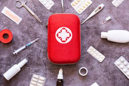 Photo pour Home first aid kit, pills, thermometer on plain background - image libre de droit