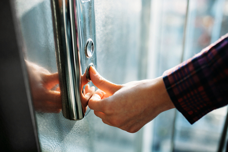 Foto de The thumb presses the Elevator button, a hand reaching for the button, the girl waiting for Elevator, push button start, isolated - Imagen libre de derechos