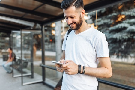 photo of a beautiful stylish Guy, in a blank white t-shirt, hipster looking at the phone standing at the bus stop waiting for transport, n