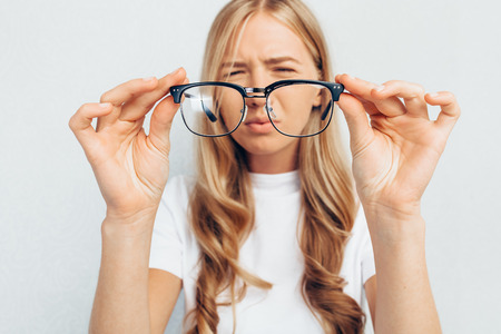 Photo for Young girl wearing white t-shirt, holding glasses, selective focus on glasses, standing on gray background, Concept: poor eyesight - Royalty Free Image