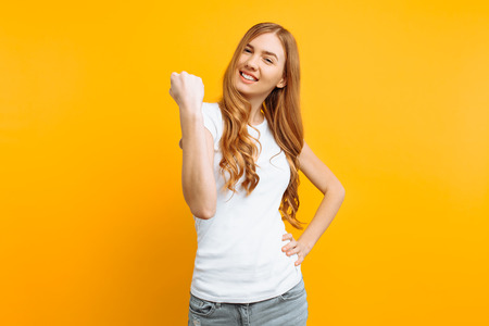 Portrait of a happy girl in a white T-shirt, with fists raised, celebrating a victory on a yellow background. The concept of achievement.