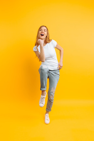 Photo pour Full length, enthusiastic girl in a white T-shirt, celebrating success on a yellow background - image libre de droit