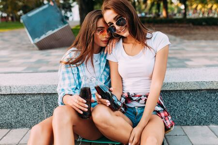 Photo pour Two stylish girlfriends in shorts and sunglasses, drink a drink sitting in the Park - image libre de droit