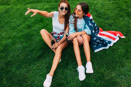 Photo pour Two attractive young girls in sunglasses sitting in the Park on the lawn with the American flag, with a refreshing drink. U.S. independence day celebrations - image libre de droit