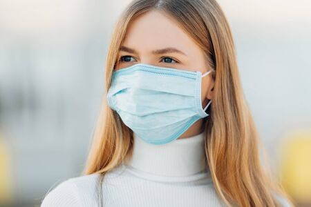 Photo pour A young girl in the background of a building wears a face mask that protects against the spread of coronavirus disease. Close- up of a young woman with a surgical mask on her face against SARS-cov-2. - image libre de droit