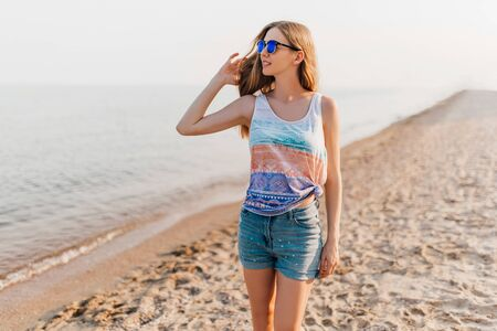 Photo for Attractive young girl in sunglasses, strolling along the beach enjoying the Sunny weather. - Royalty Free Image