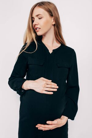 Photo pour Beautiful pregnant woman in black dress posing on a white background, fashion photography pregnancy - image libre de droit