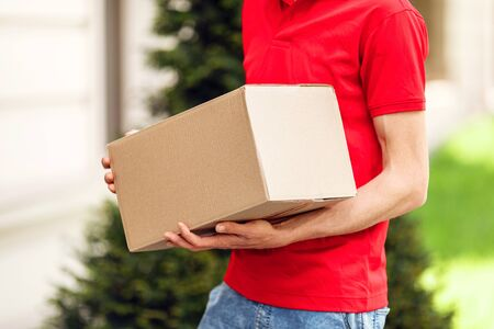 Photo for Courier with parcels in hand in the open air - Royalty Free Image