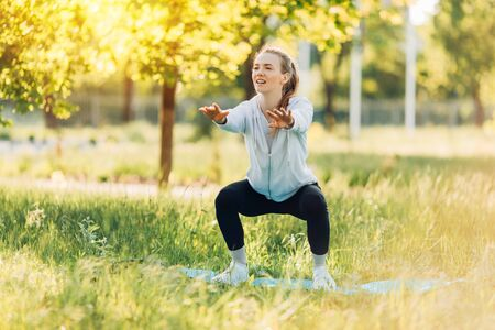 Photo pour Athletic young woman doing sports in the Park in the morning, women's workout on a yoga Mat - image libre de droit