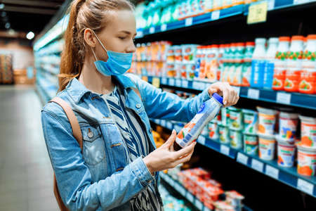 Photo pour young woman in a medical protective mask on her face buys food at a supermarket. a young lady buys dairy products at a grocery store. Sale, purchase, nutrition, coronavirus - image libre de droit