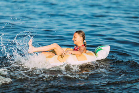 Photo pour Happy child on an inflatable circle floating on the sea, Summer holidays with children. Swimming equipment and clothing for children. - image libre de droit