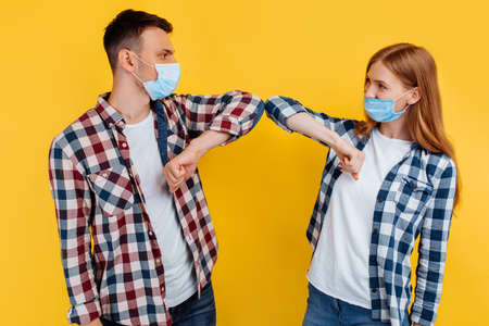 Photo for Portrait of a man and woman in plaid shirts and medical protective masks greeting each other with their elbows, on an isolated yellow background - Royalty Free Image