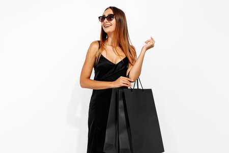 Photo pour young woman in black dress and sunglasses, with shopping bags on a white background, shopping concept, Black Friday - image libre de droit