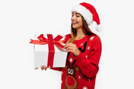 Photo pour Cheerful young woman in a Christmas sweater and Santa Claus hat, with a gift on a white background, the concept of Christmas, New Year - image libre de droit