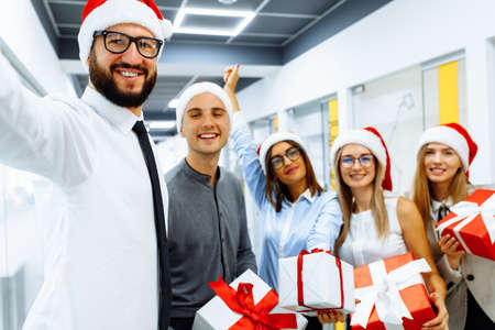 Photo pour Happy group of businessmen in Santa Claus hats, with Christmas gifts are having fun celebrating New Year and taking selfie on a mobile phone - image libre de droit