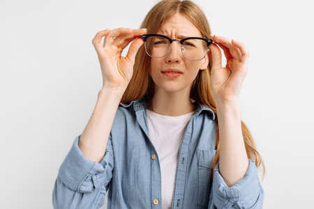 Photo pour Poor eyesight. Young woman with glasses squinting, trying to take a closer look, woman with poor eyesight on white background - image libre de droit