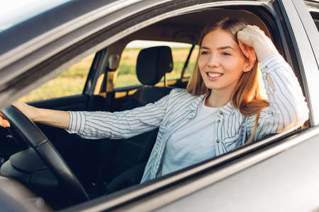 Photo pour Beautiful young happy smiling woman driving her new car at sunset - image libre de droit