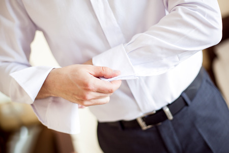 Photo pour a man fastening a cuff - before getting married - image libre de droit