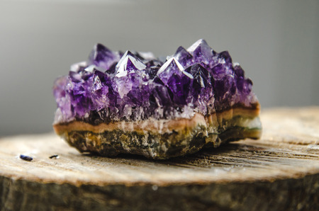 Raw violet amethyst rock with reflection on natural wood macro crystal  ametist esoteric