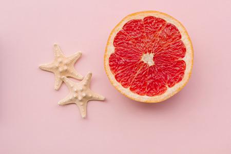 Foto de Fashion. Tropical Fresh Summer Set. Fashion Design. Fruit Citrus. Grapefruit. Bright Color. Creative Art. Minimal. Fashion Top View. Summer Beach Concept. Sea stars - Imagen libre de derechos