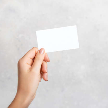 Photo pour Female hand holding a blank business card, cutaway on gray concrete background with copy space. - image libre de droit