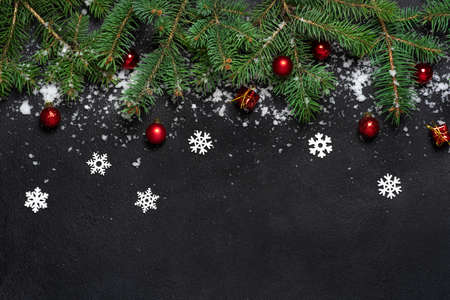 Photo pour Christmas or New Year decoration background. For fir tree branches on black background with copy space. Flat lay. Pattern. White snowflakes and snow, red balls. - image libre de droit