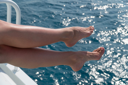 young female legs hanging over the sea water.の写真素材