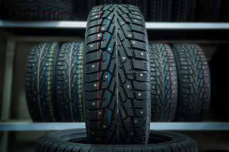 Photo pour Winter tire on the background of racks with tires. - image libre de droit