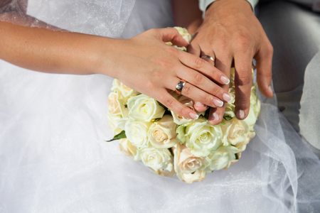Foto de Bride and groom hold hands with golden wedding rings above wedding bouquet from white roses, cream flowers. - Imagen libre de derechos