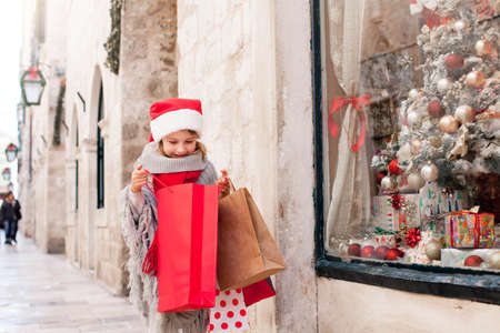 Photo for Christmas shopping. Child girl looks into paper bags on market street. Cute kid in red santa hat makes purchase by store showcase decorated with gifts. Cozy fair, New Year and Black Friday - Royalty Free Image