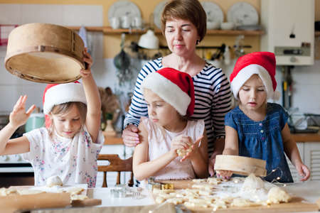 Photo pour Family is cooking Christmas gingerbread cookies together in cozy home kitchen for dinner. Kids and young grandmother prepare holiday meal. Girls help woman. Lifestyle moment. Children chef concept - image libre de droit