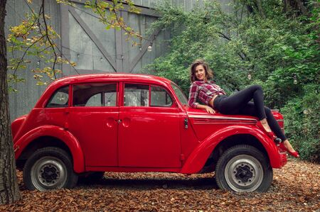 Pin-up girl in jeans and a plaid shirt is posing on a russian red retro car. She is looking at the camera and smiling happily.