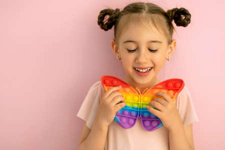 Photo pour A beautiful cute little girl with her eyes closed holds a butterfly-shaped popit toy in her hand. Funny pigtails for girls. These are children's entertainment and educational toys. Pop it toy - image libre de droit